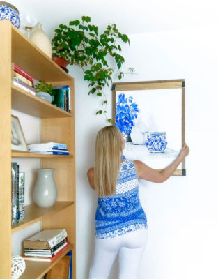 Artist hanging an artwork in a decorated interior