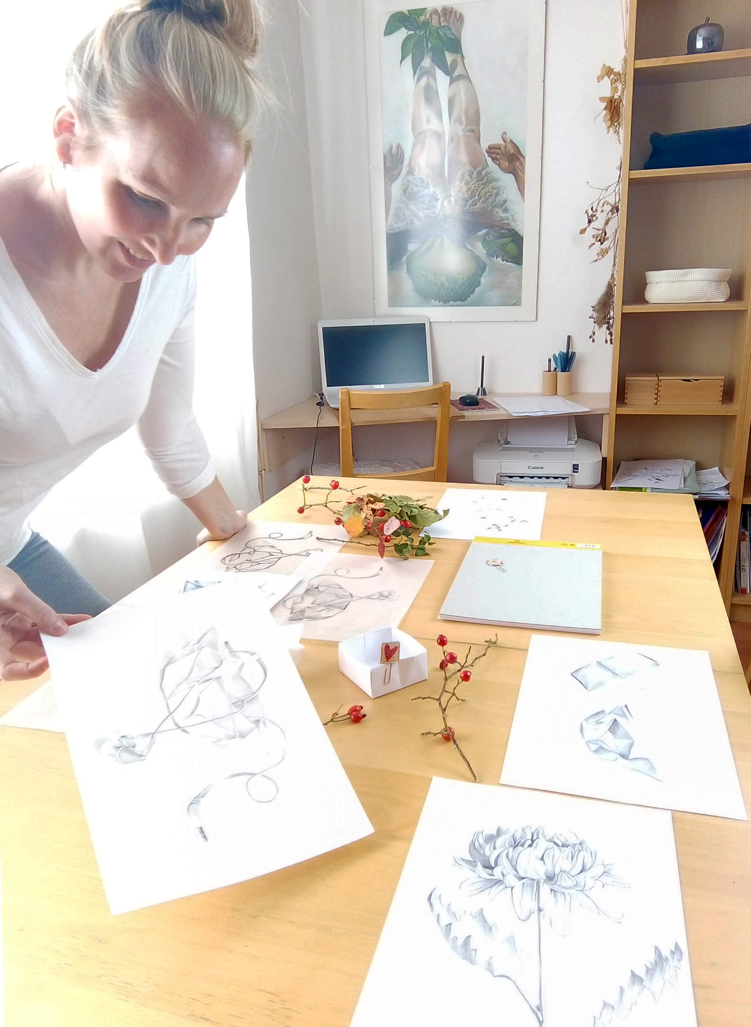 woman holding a drawing by table